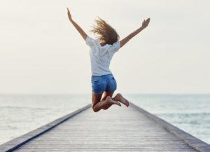Vacation Marketing: Girl jumping on a boat dock at the lake